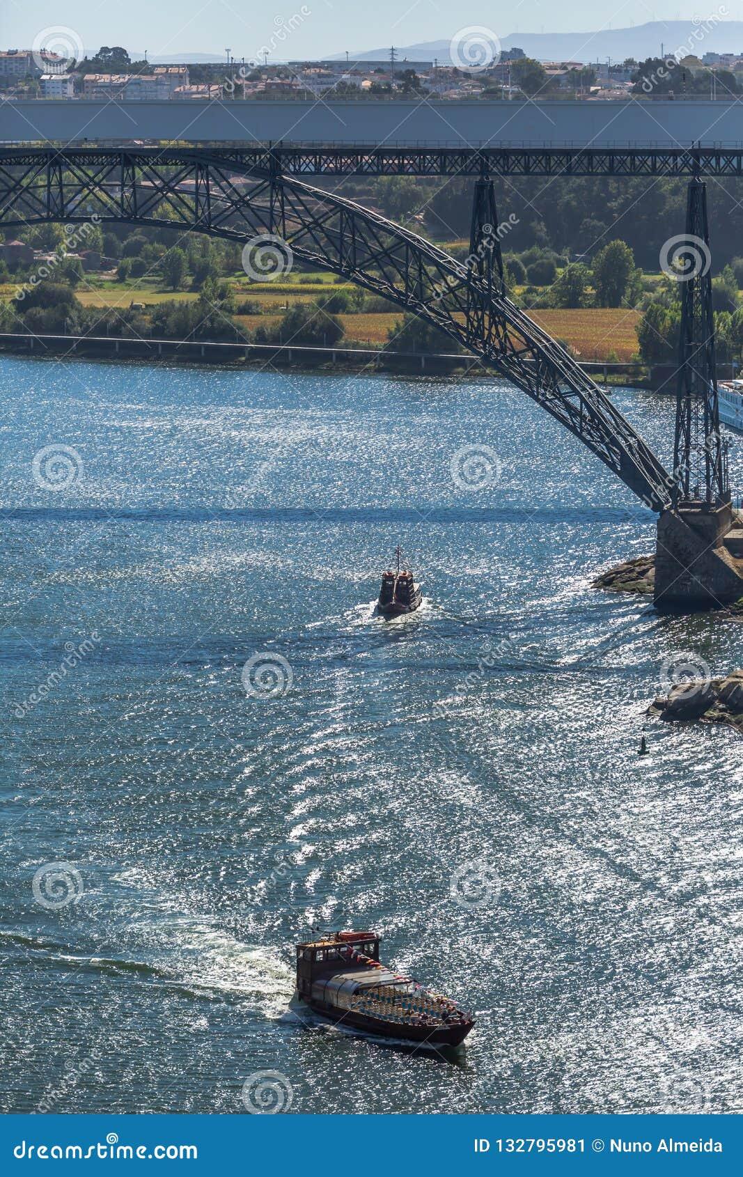 Vista del río el Duero y de los puentes D Maria Pia y el infante, los bancos y los barcos navegando en el río