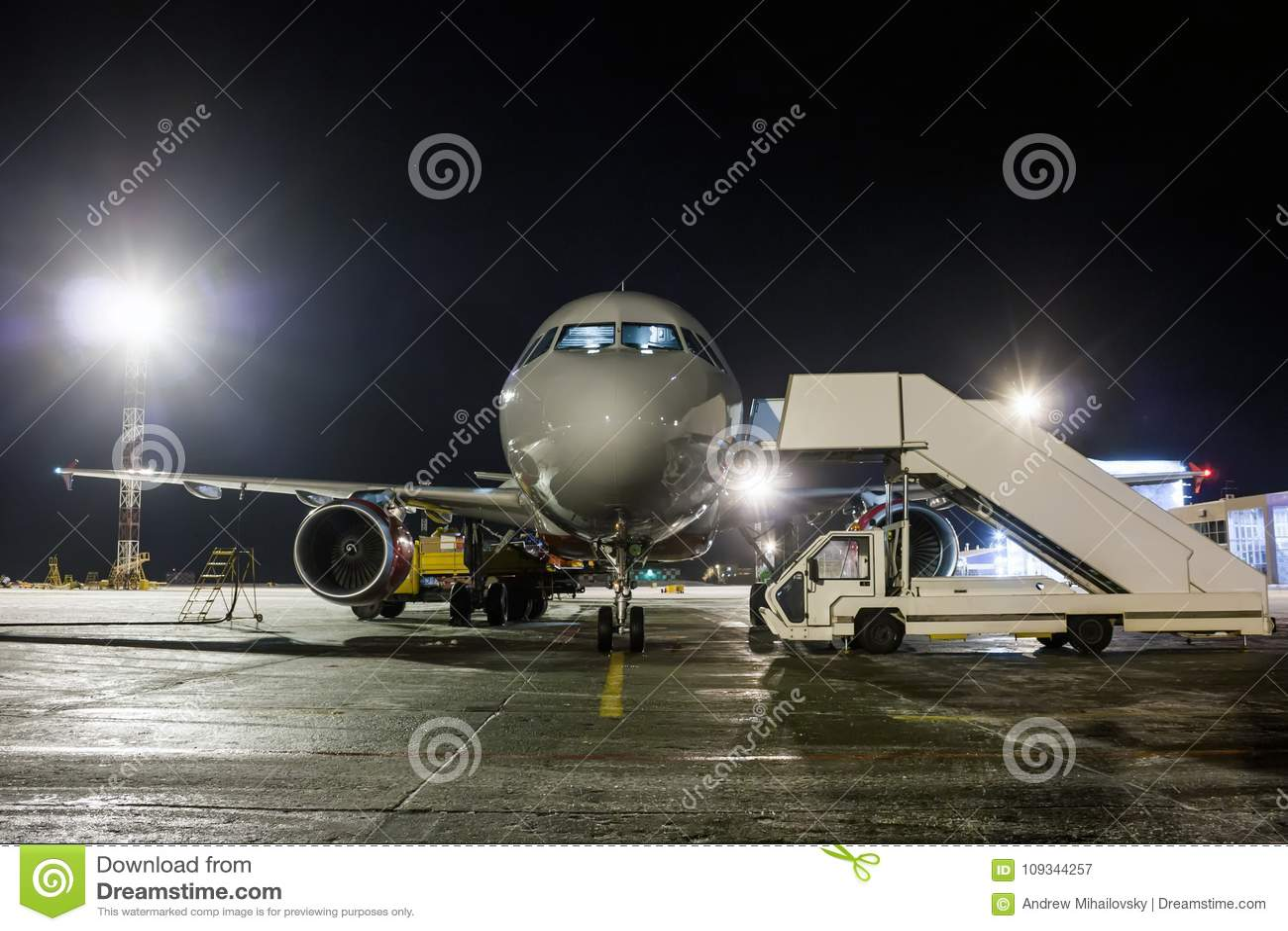 Vista delantera del aeroplano del pasajero del servicio en tierra en la noche