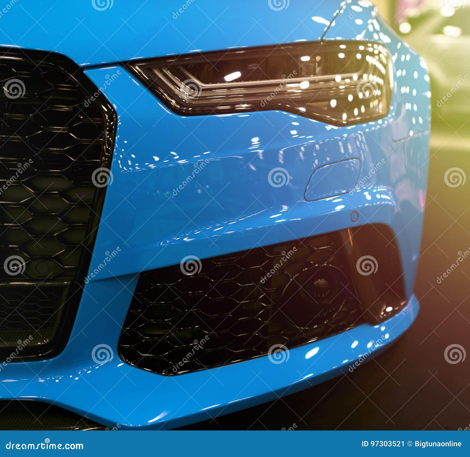 Vista delantera del deporte de lujo moderno azul con la luz anaranjada suave del sol Detalles del exterior del coche Linterna de