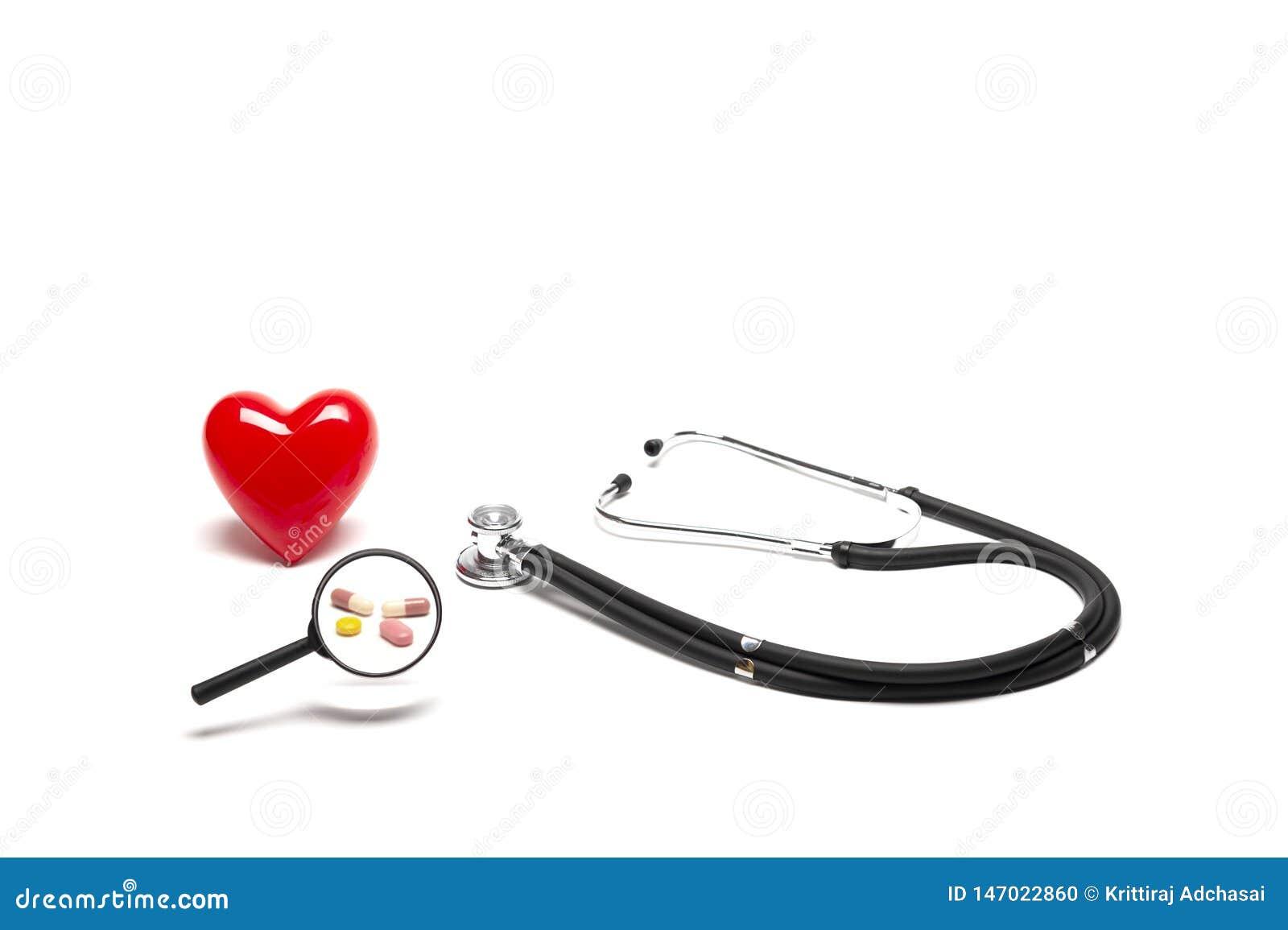 Vista delantera del modelo, de los estetoscopios, y de las drogas rojos plásticos del corazón con la lupa en el fondo blanco