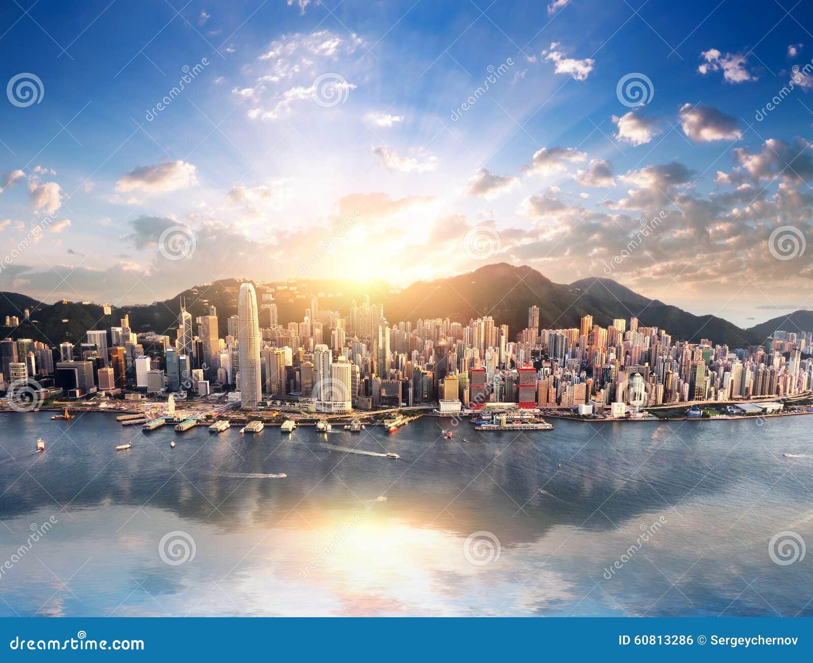 Vista dell orizzonte della città di Hong Kong dal porto con i grattacieli ed il sole