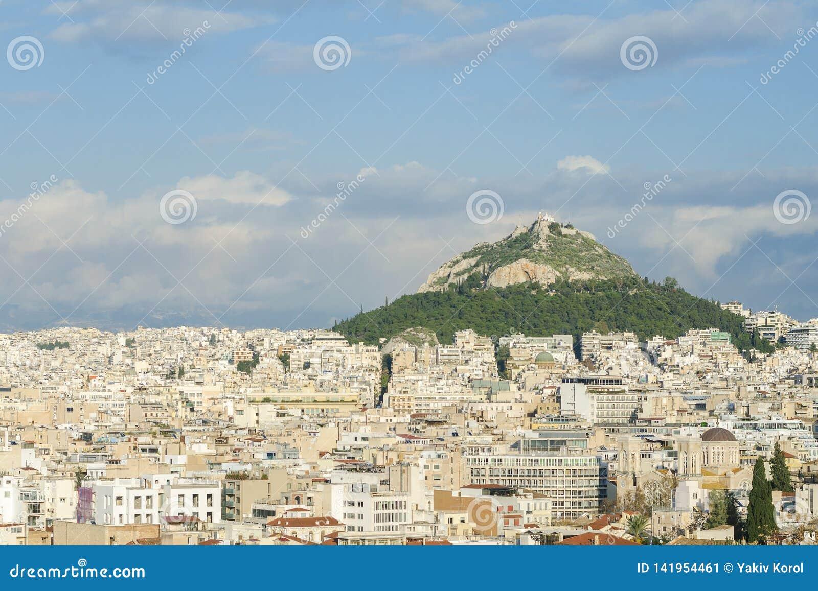 Vista della città di Atene e una grande montagna con un monastero sulla cima Bello cielo blu