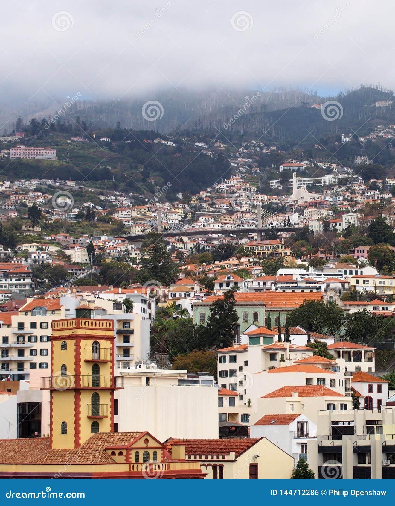 Vista della città di Funchal in Madera con la vecchie chiesa e case con il ponte e le montagne della strada nella distanza