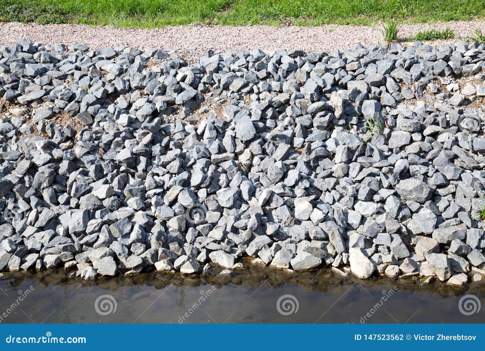 Vista della protezione della costa delle pietre grige del granito