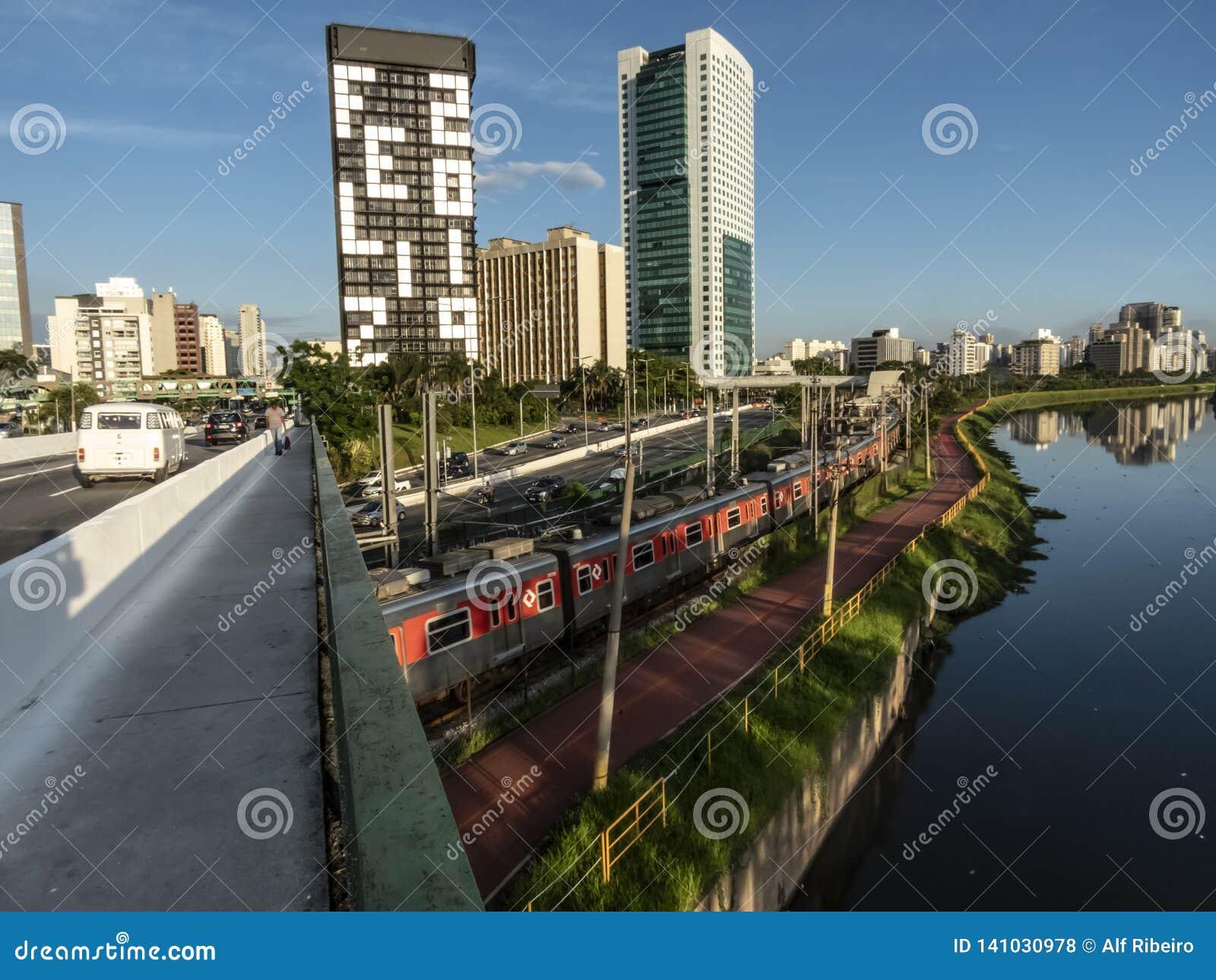 Vista delle costruzioni, del treno di CPTM, del traffico dei veicoli e del fiume nel viale marginale del fiume di Pinheiros