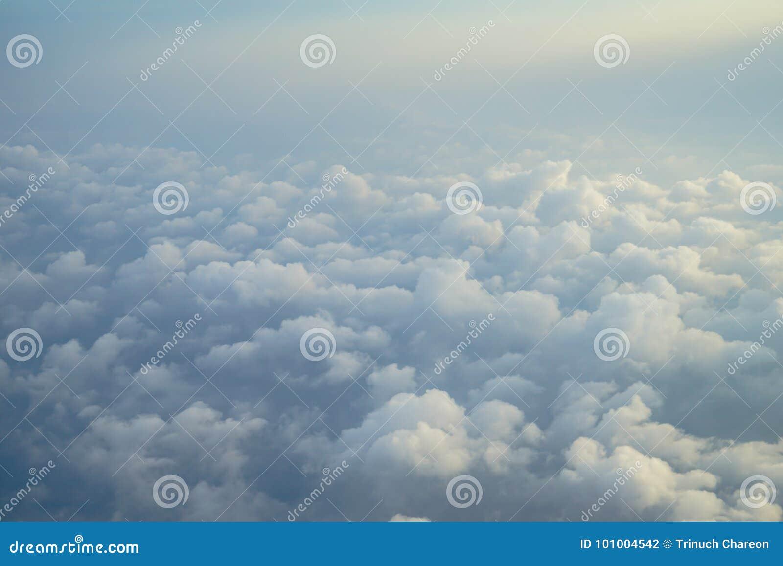 Vista di bella nuvola bianca astratta lanuginosa vaga con cielo blu e del fondo leggero di alba dalla finestra dell aeroplano