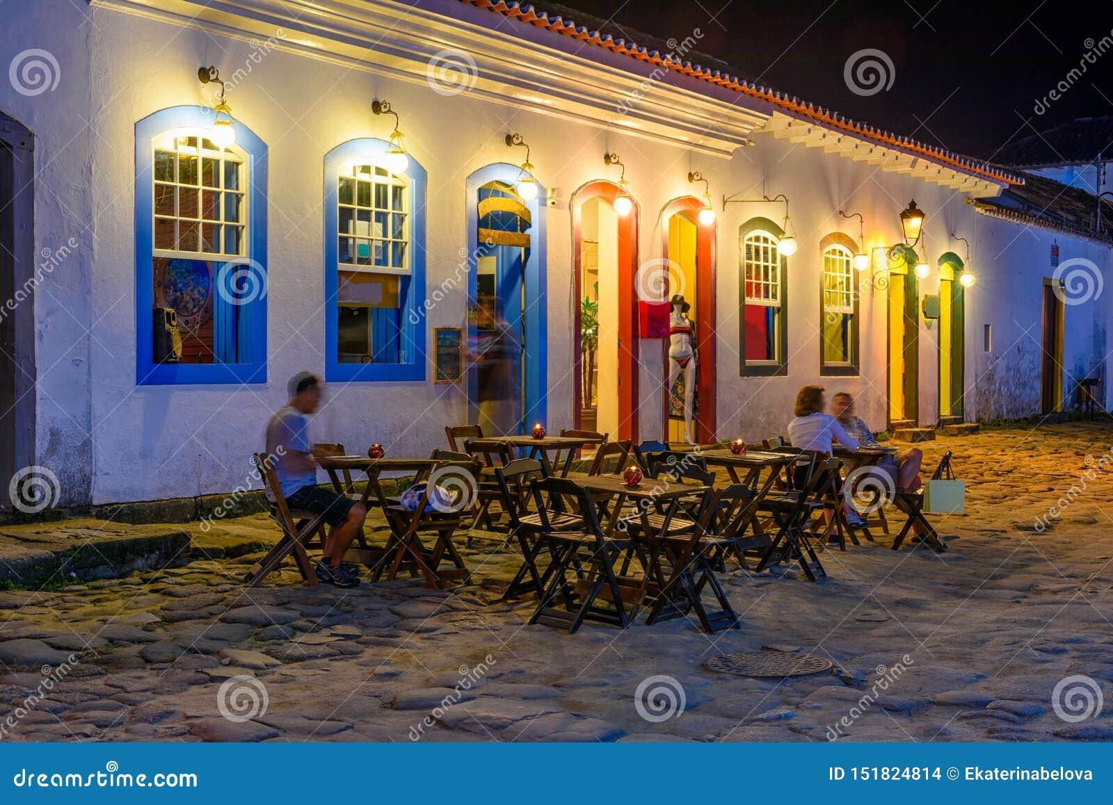 Vista di notte della via del centro storico con le tavole del ristorante in Paraty, Rio de Janeiro, Brasile