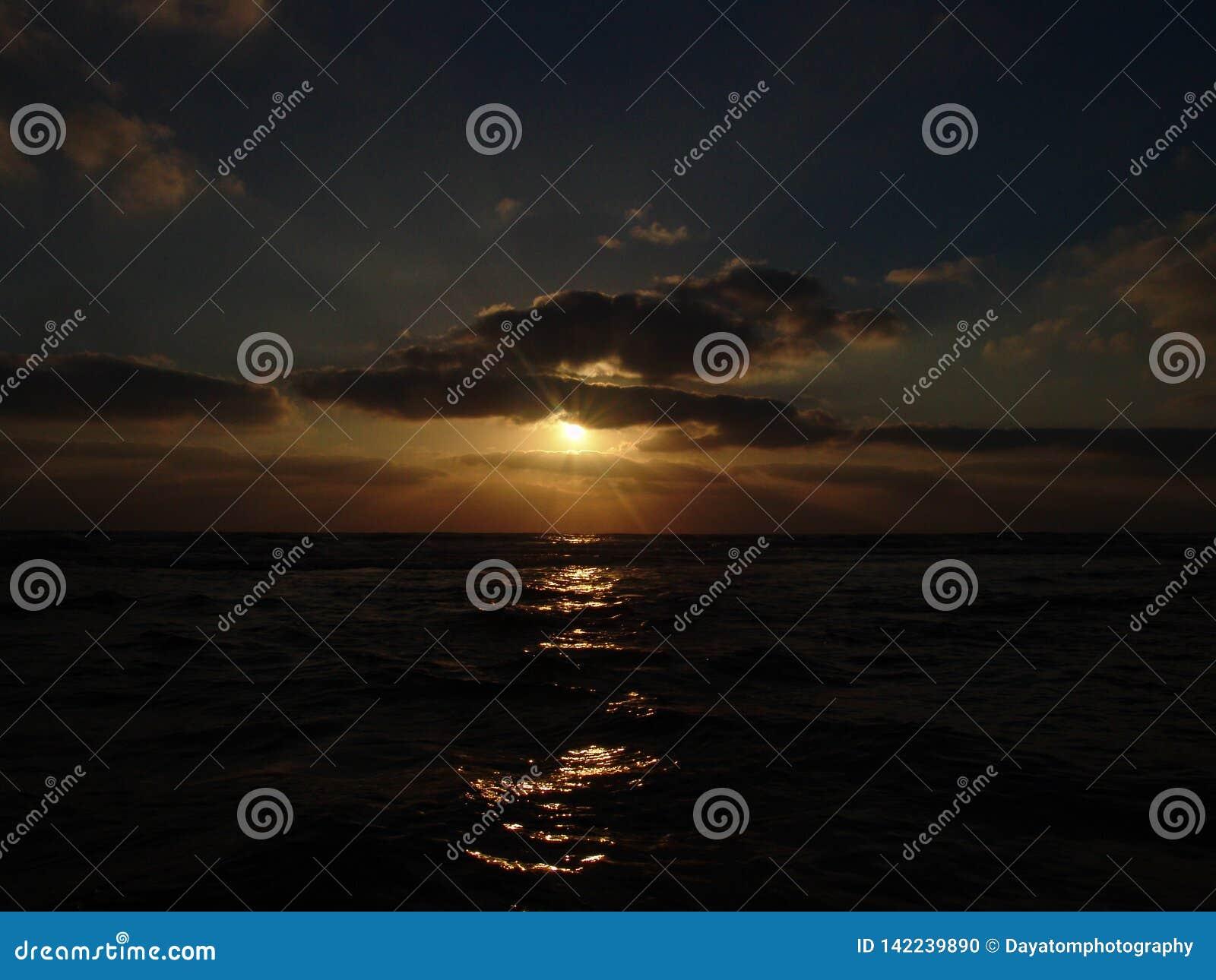 Vista di tramonto su una spiaggia sabbiosa calma con il cielo nuvoloso e la luce dorata