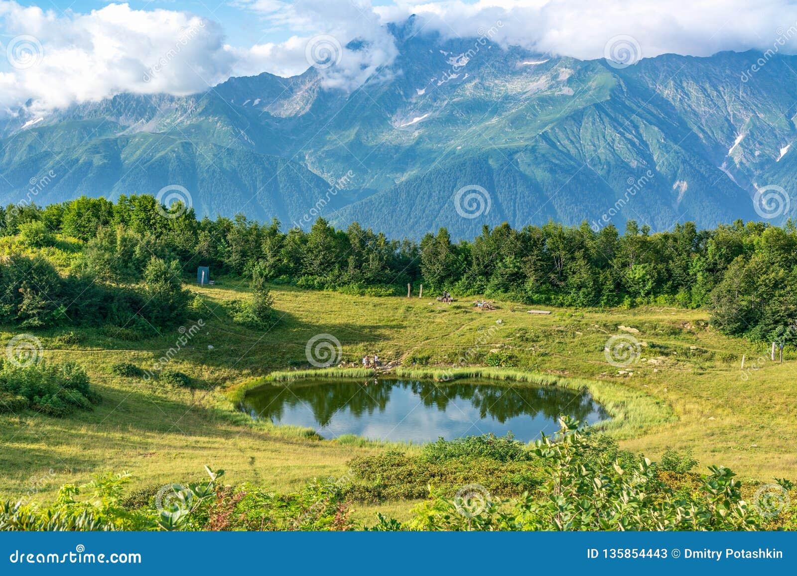 Vista di una radura della montagna con un lago trasparente dello specchio e turisti, circondati da erba ed alberi e alte montagne