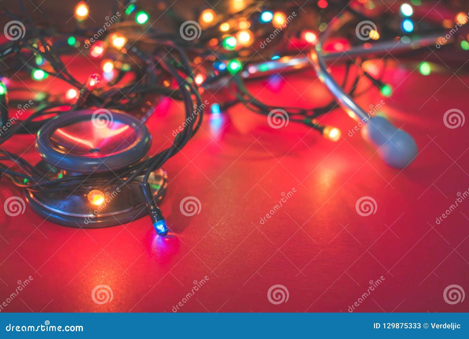 Vista di uno stetoscopio rosso che si trova sul fondo rosso con le luci di Natale variopinte