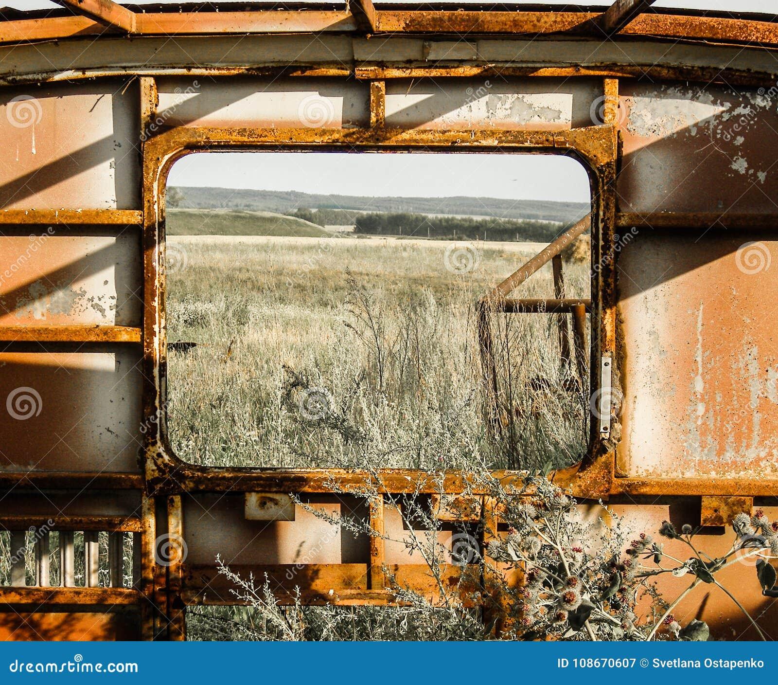 Vista do campo e da floresta através da janela de um ônibus oxidado velho