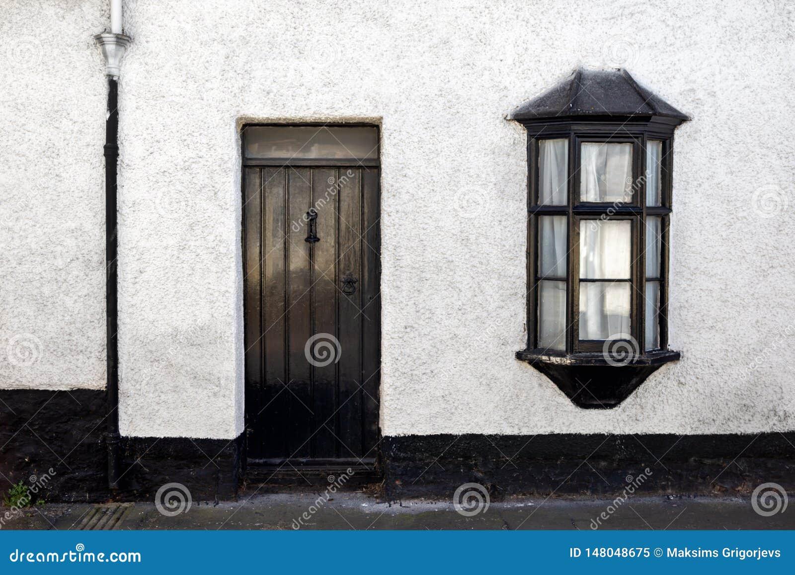 Vista esteriore di bello vecchio cottage di pietra inglese con la porta e la finestra