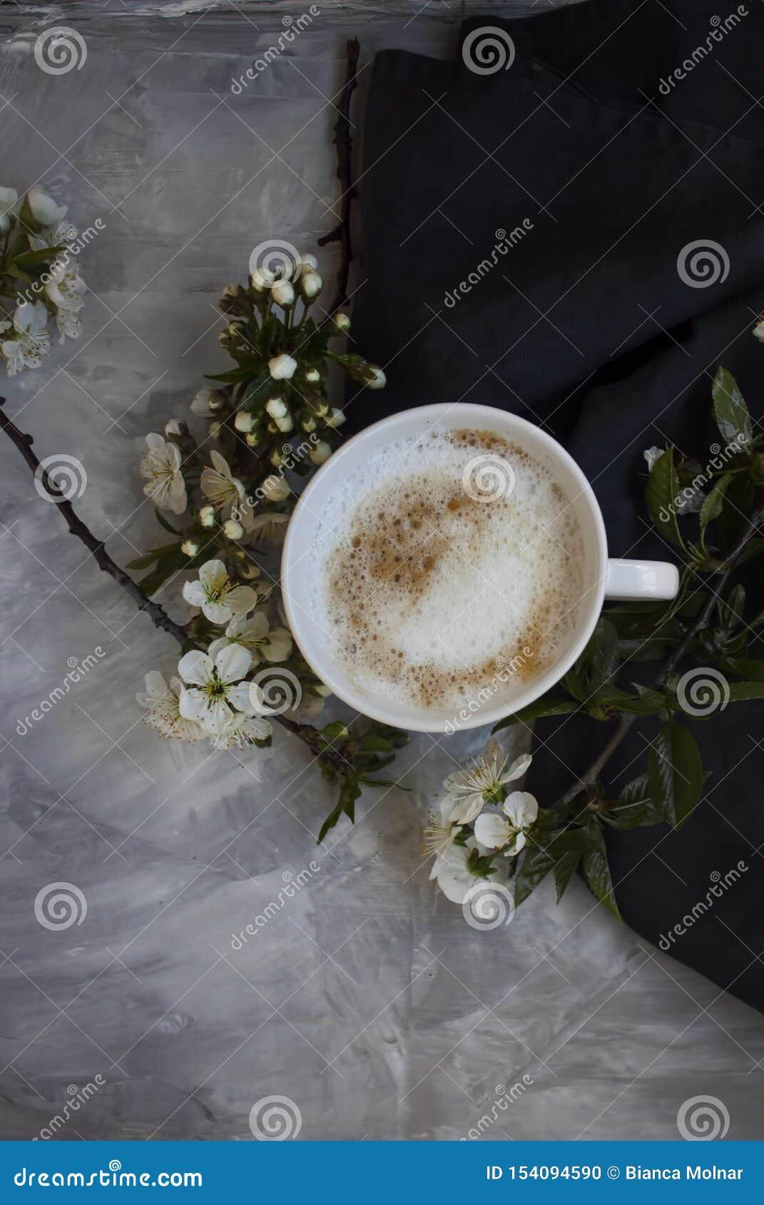 Vista geral da xícara de café quente com flores brancas