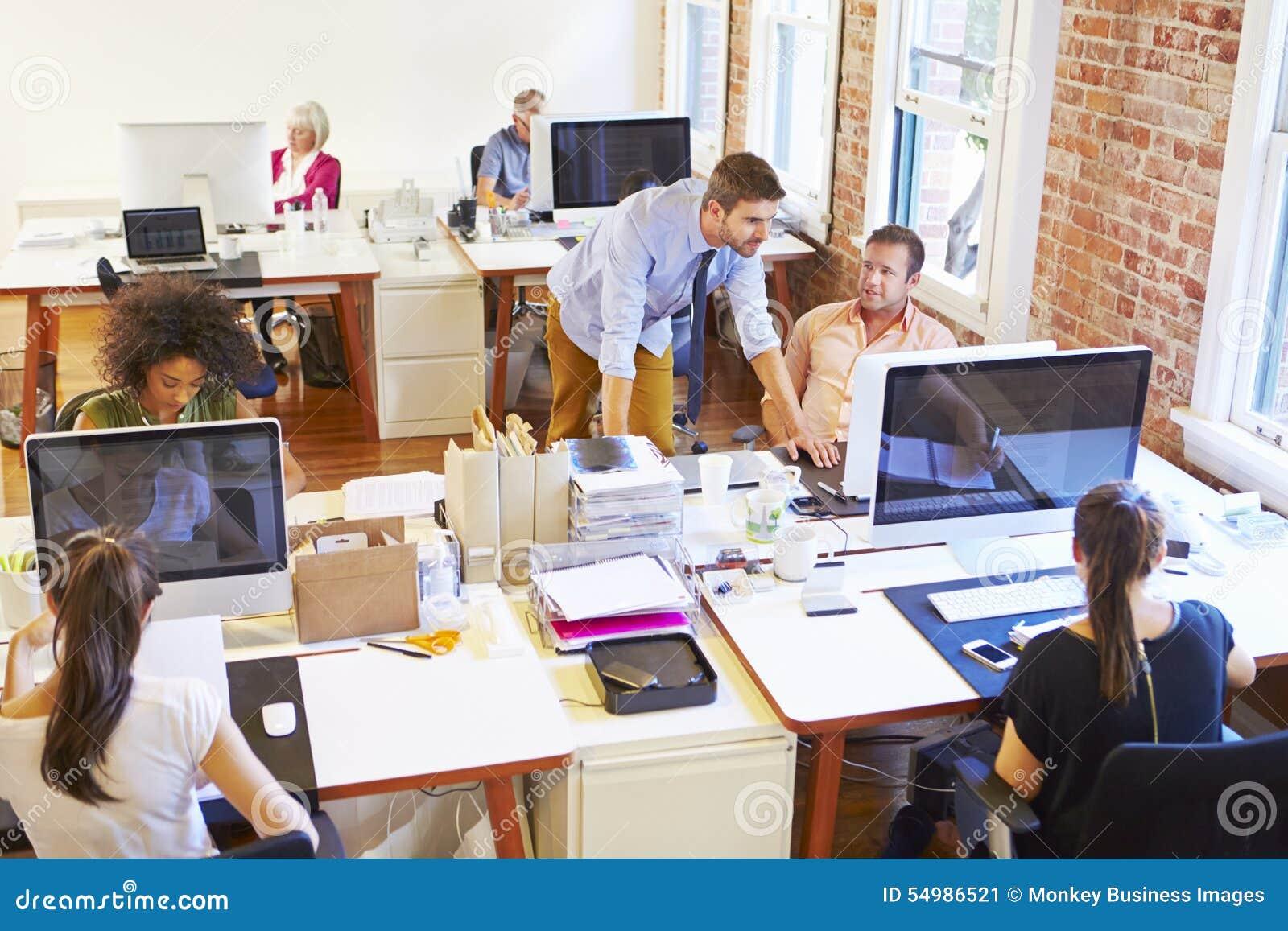 Vista granangular de la oficina conceptora ocupada con los trabajadores en los escritorios