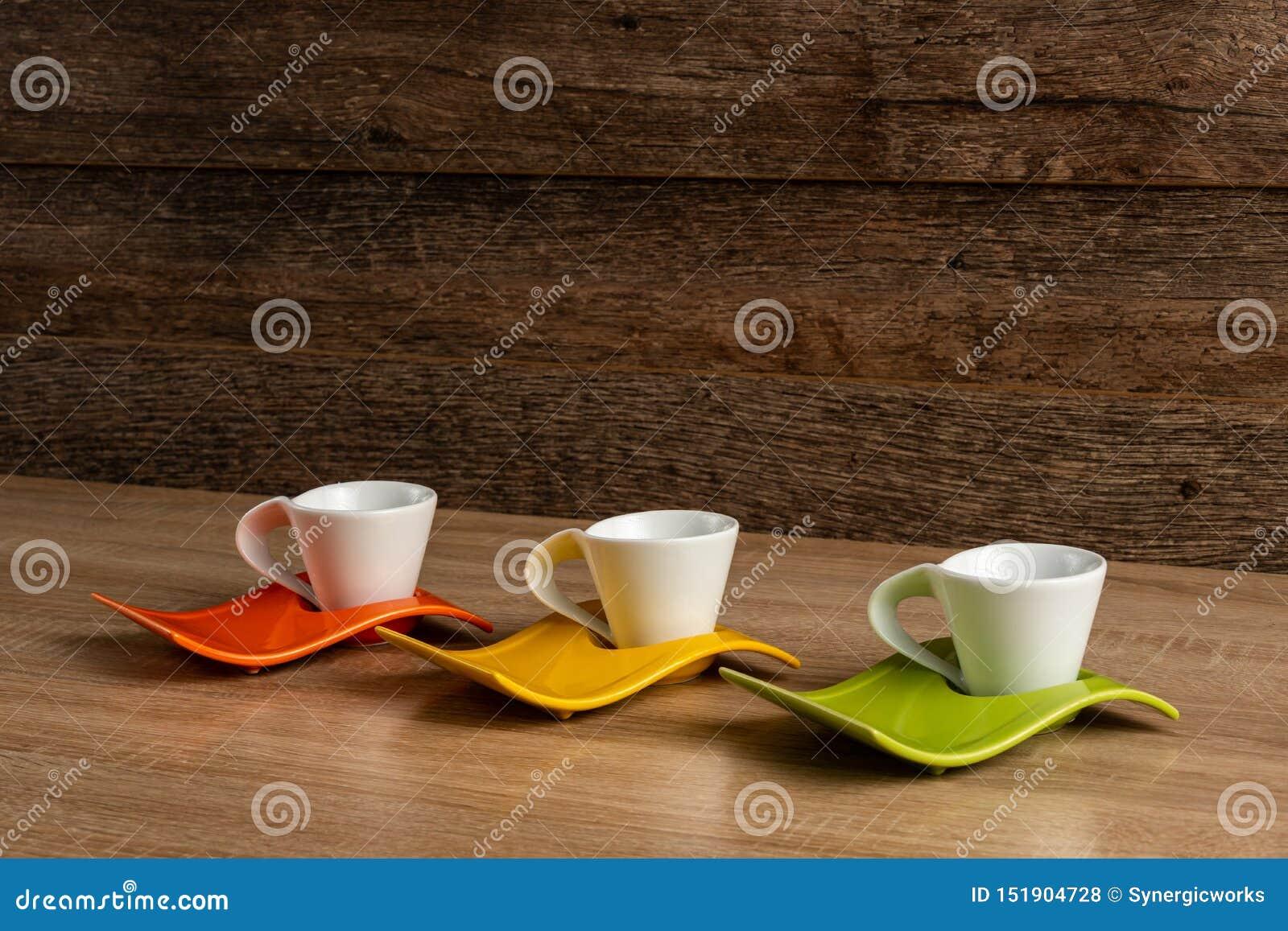 Vista inclinada de izquierda a derecha lateral del lugar de las tazas del café con leche en tres placas de los colores