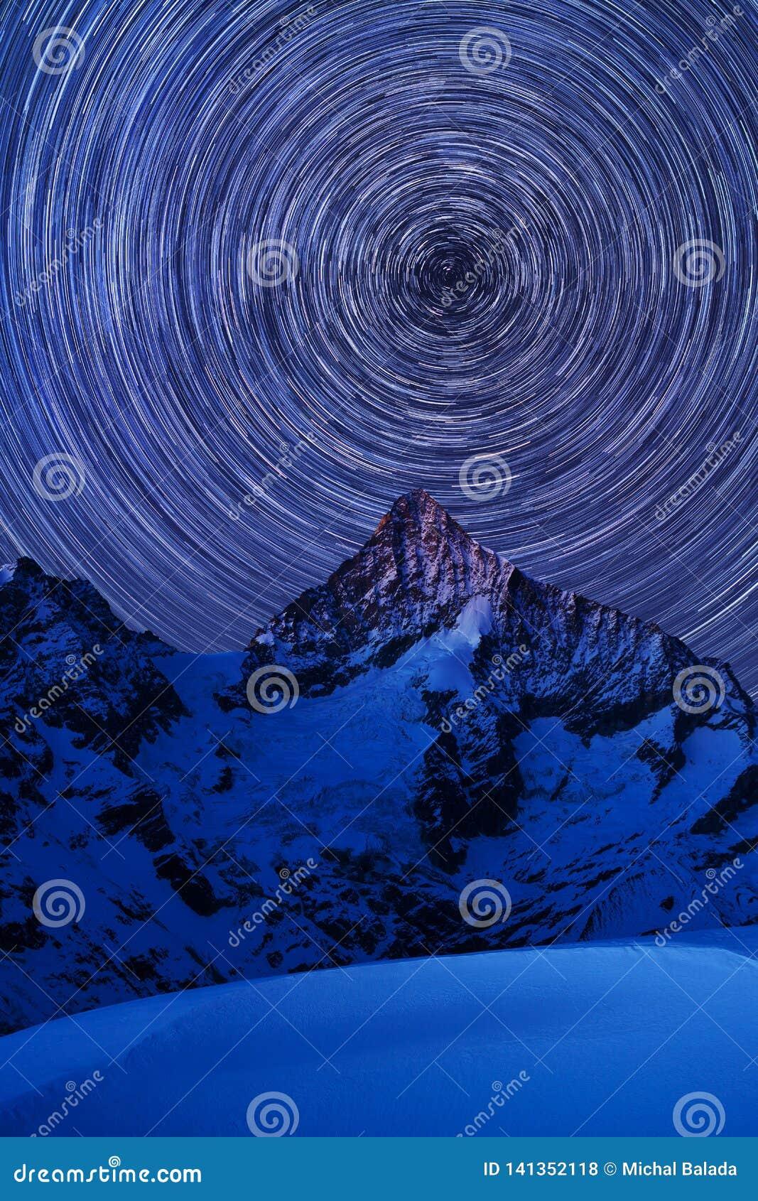 Vista incredibile di notte in alpi svizzere Tracce della stella che si muovono in cielo blu Posizione della località di soggiorno