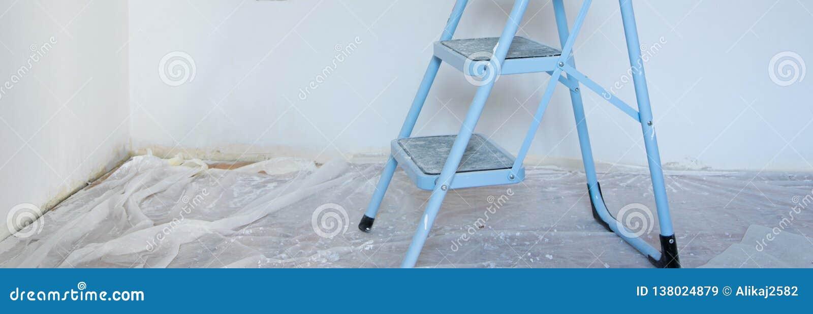 Vista interior del emplazamiento de la obra, de la escalera en primero plano y de paredes de pintura frescas con el color blanco