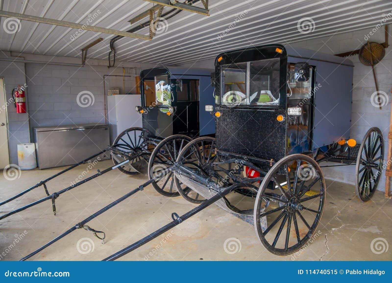 A vista interna do transporte ou do carrinho do preto de Amish estacionou dentro de uma garagem de uma casa no Condado de Lancast