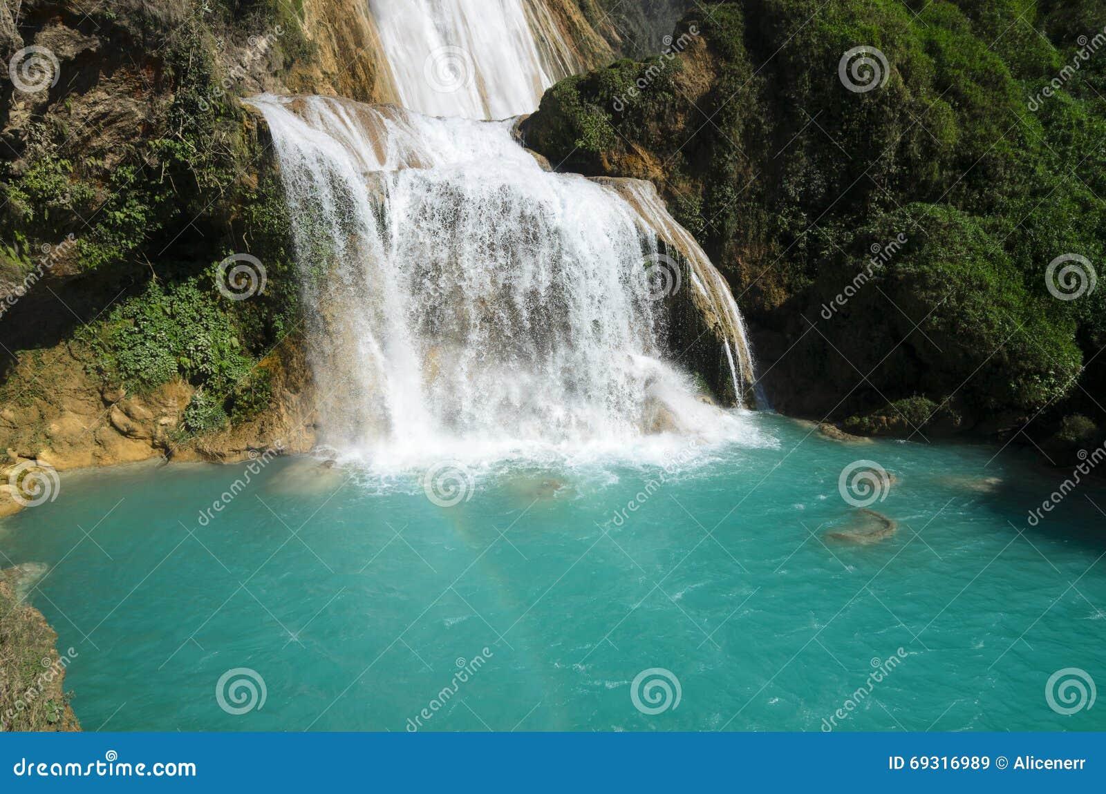 Vista a la cascada asombrosa con la piscina de la turquesa rodeada por gree