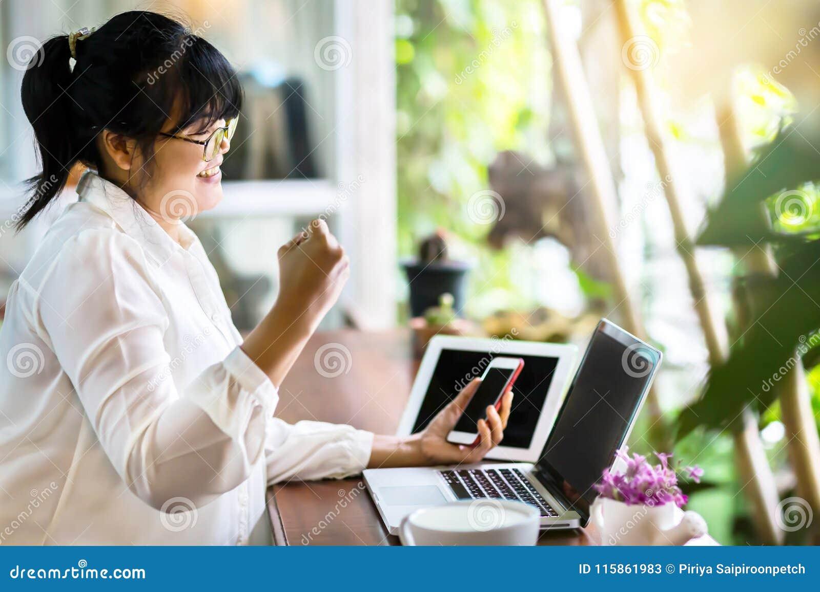 Vista lateral de la empresaria asiática que se sienta en la tabla larga en cafetería y que usa el ordenador portátil y las muestr
