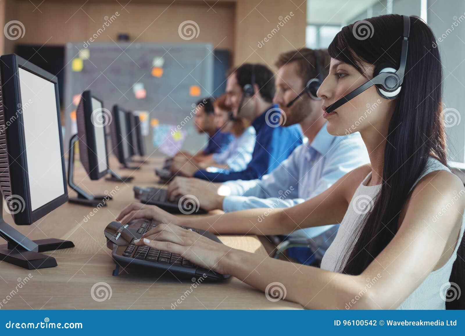 Vista lateral de la empresaria que mecanografía en el teclado en el centro de atención telefónica