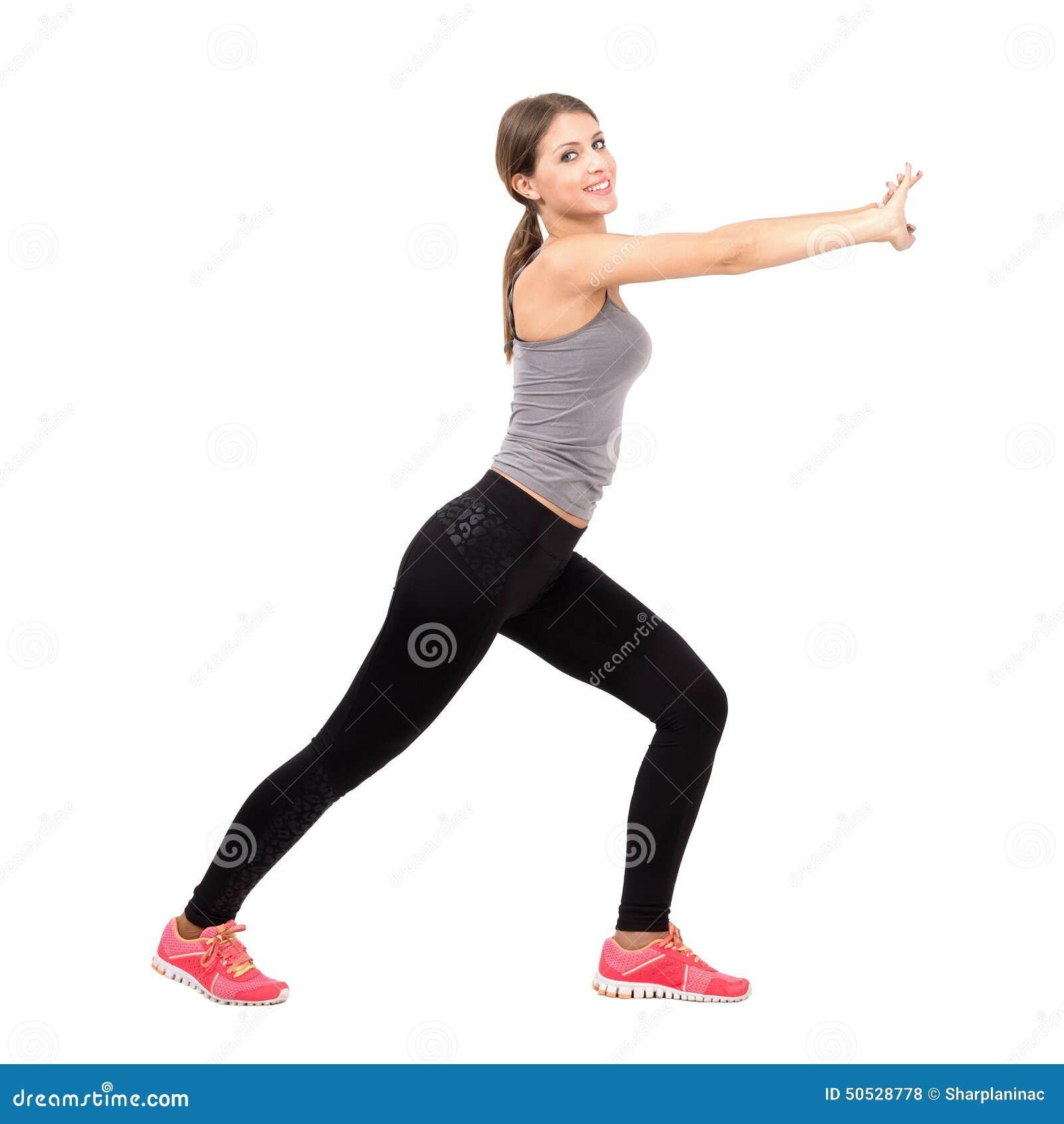 Vista lateral de la mujer deportiva delgada hermosa joven que estira y que ejercita