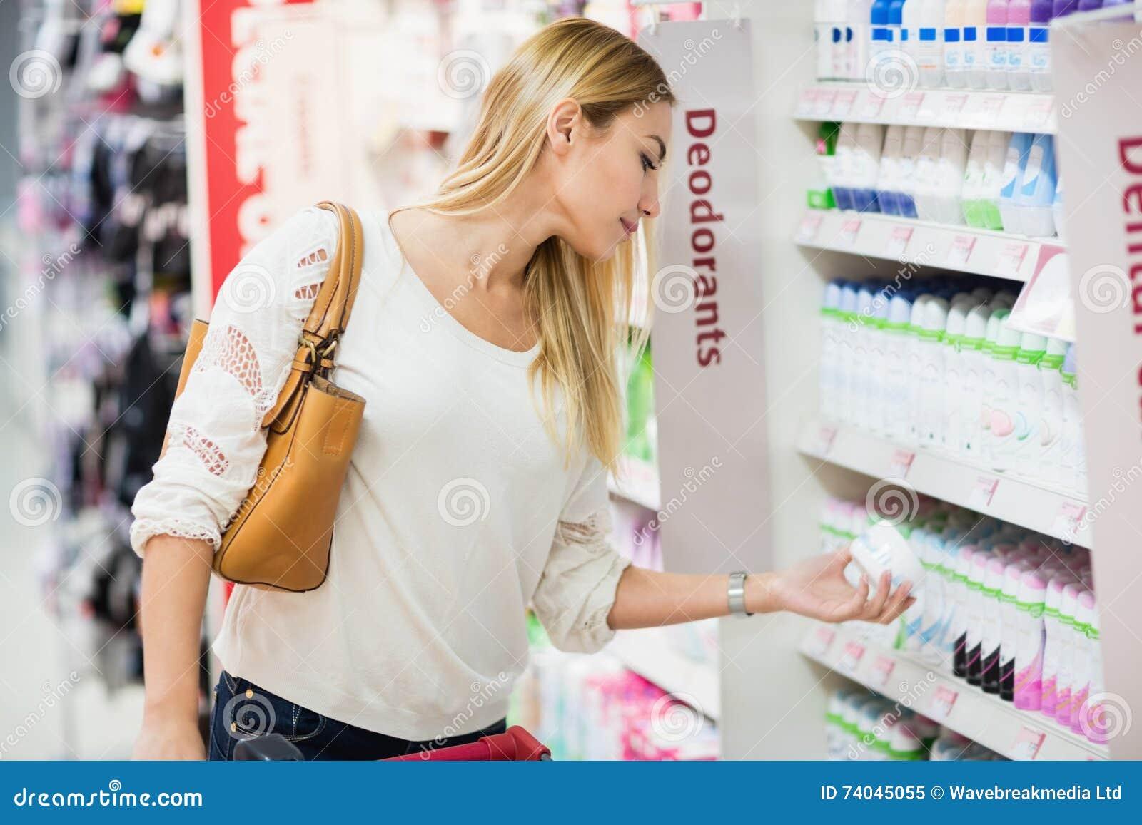 Vista lateral de la mujer que elige el desodorante