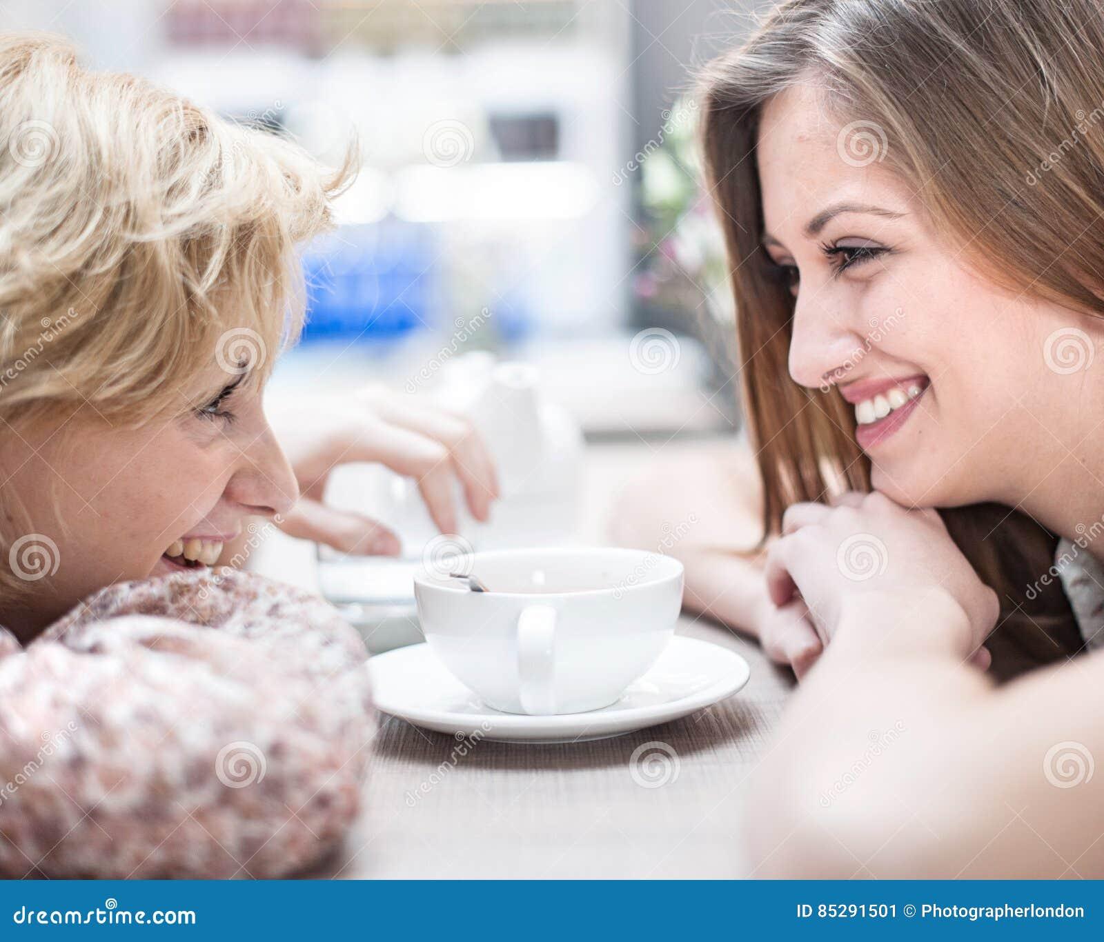 Vista lateral de los amigos femeninos jovenes sonrientes que miran uno a en café