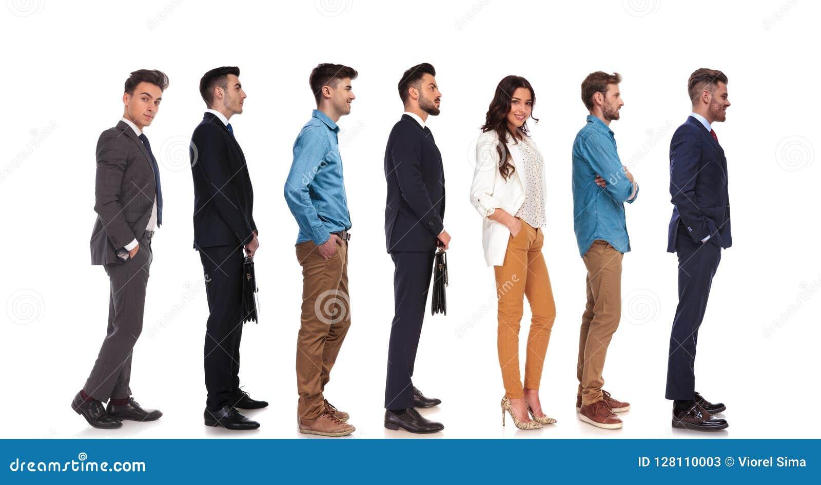 Vista lateral de siete diversas personas que se colocan en línea