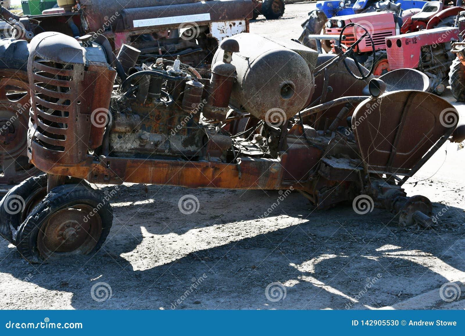 Vista lateral de um trator agrícola oxidado abandonado velho