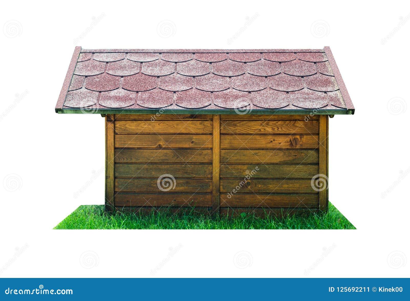 Vista lateral de uma cabana de madeira do cão com um telhado vermelho, estando na grama verde Isolado em um fundo branco com um t