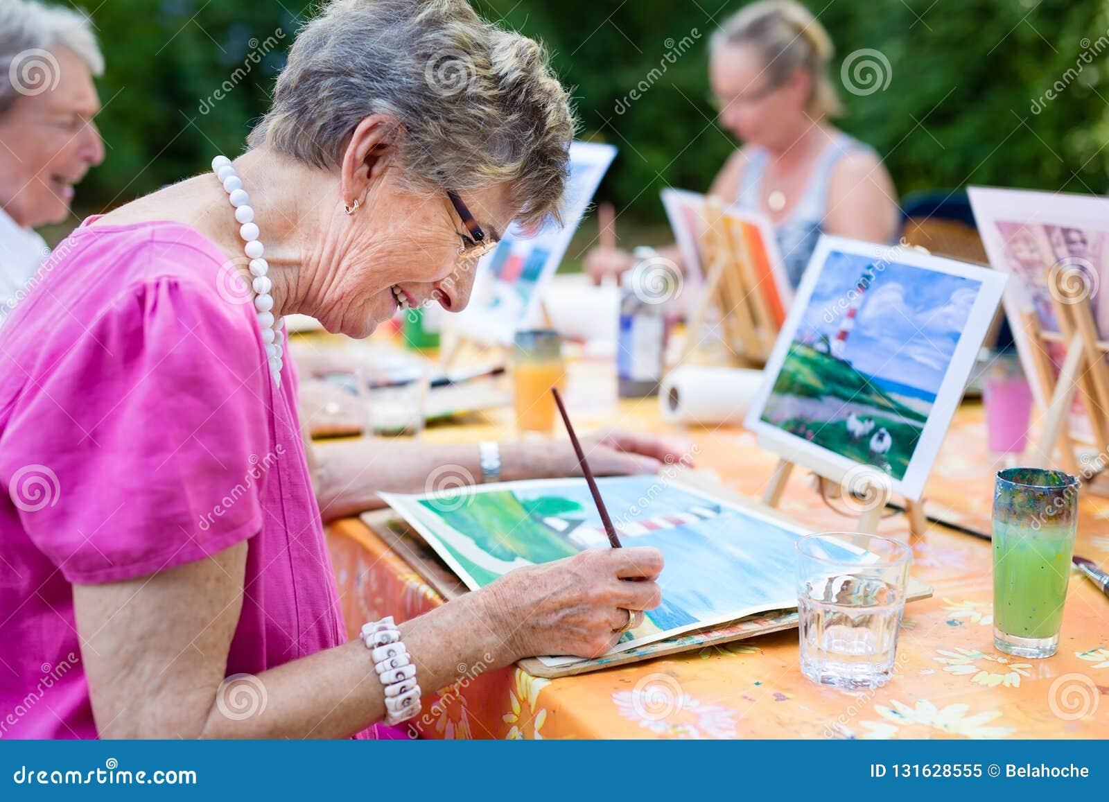 Vista lateral de una mujer mayor feliz que sonríe mientras que dibuja como aire libre recreativo de la actividad o de la terapia
