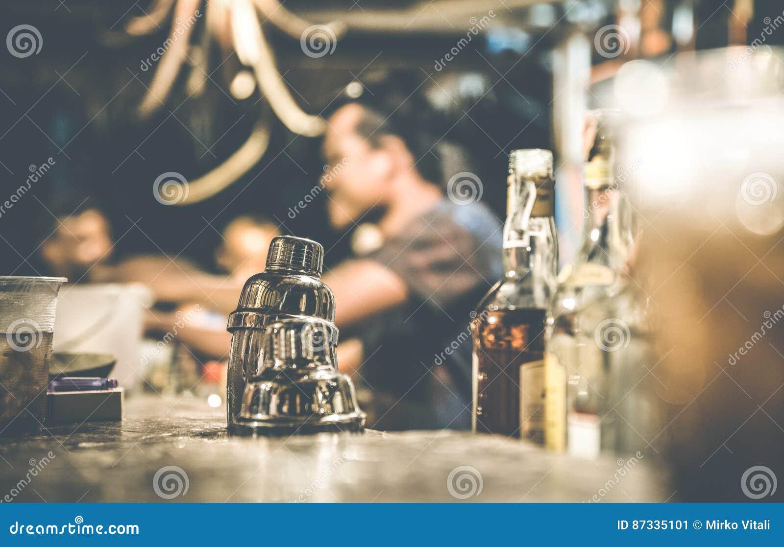 Vista lateral defocused borrosa del camarero en la barra del cóctel