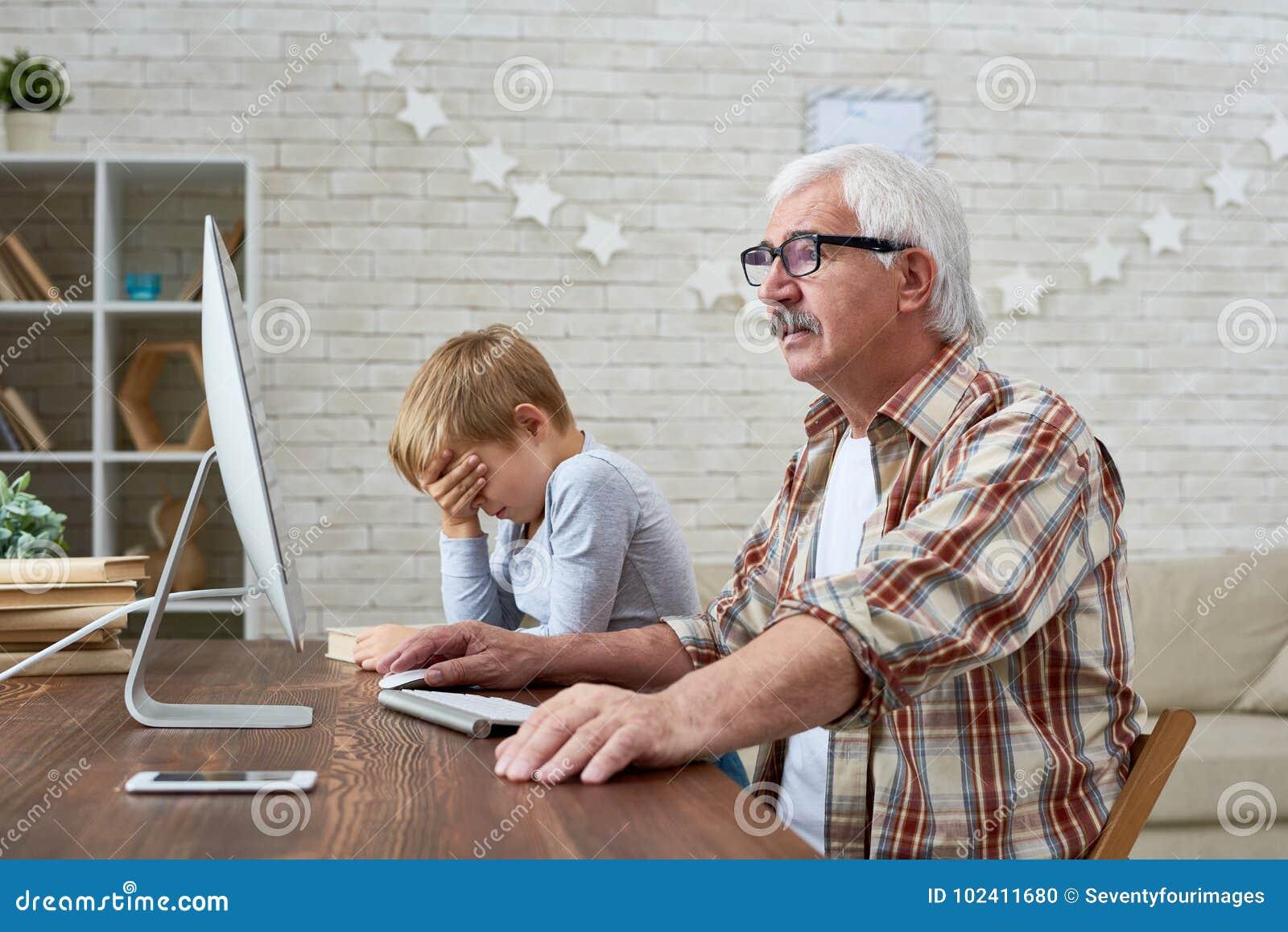 Vista lateral del viejo hombre que usa la PC