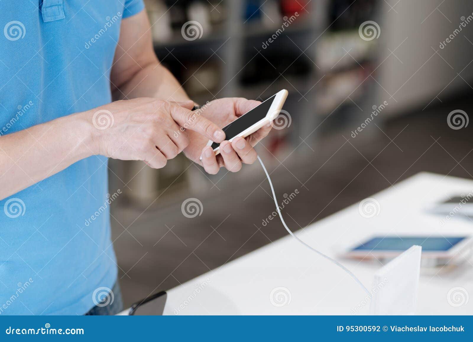 Vista lateral no homem que olha o telefone celular na loja da eletrônica