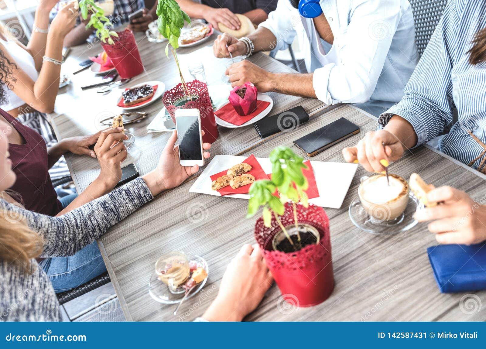 Vista lateral superior de los amigos que beben capuchino en el restaurante de la cafetería - gente que se divierte junto que come