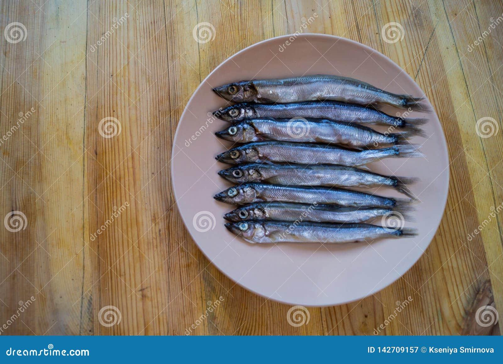 Vista laterale bassa di piccolo pesce d argento in un piatto beige su una tavola di legno, fine su