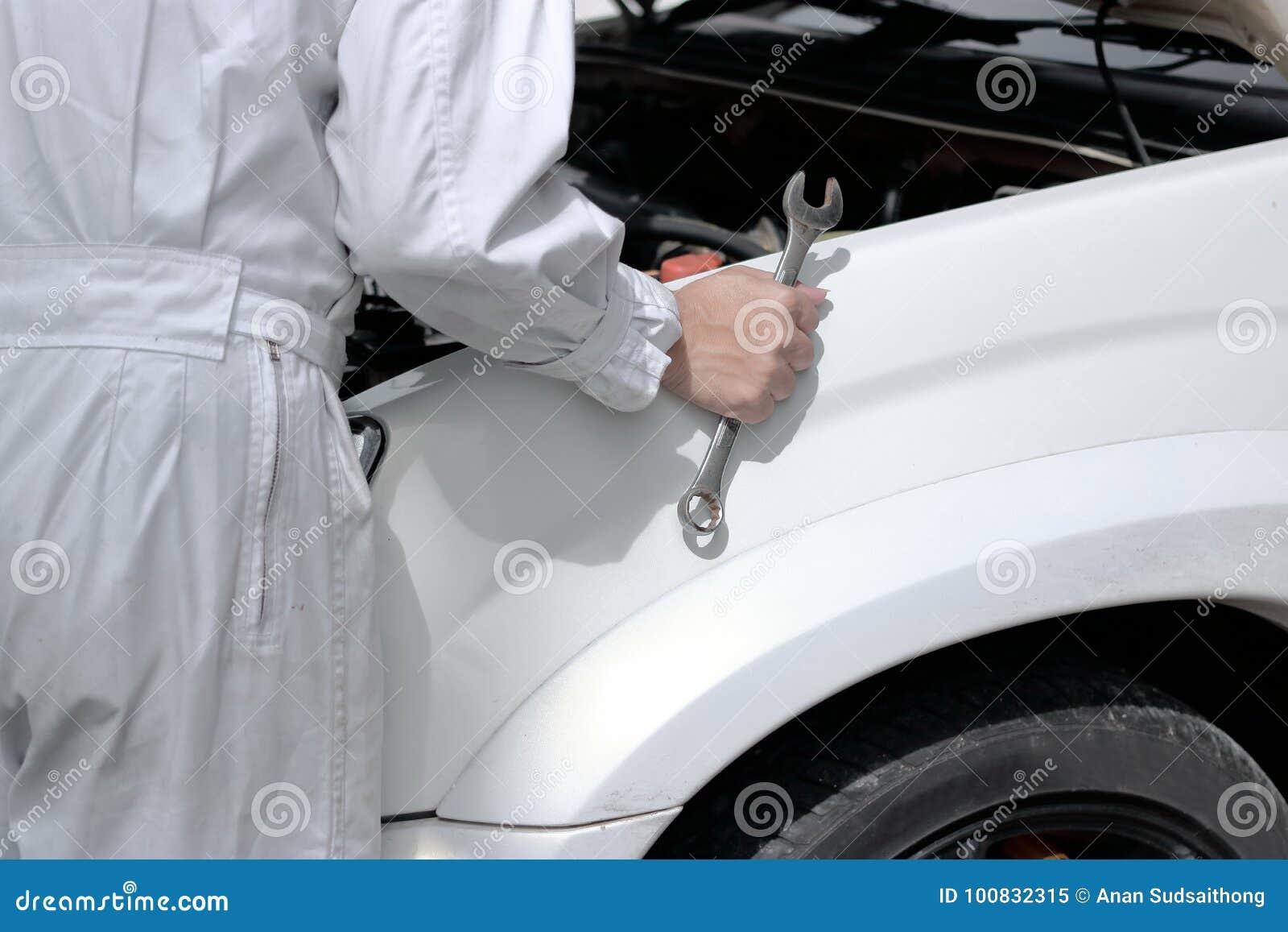 Vista laterale del meccanico automobilistico in uniforme con la chiave che diagnostica motore sotto il cappuccio dell automobile