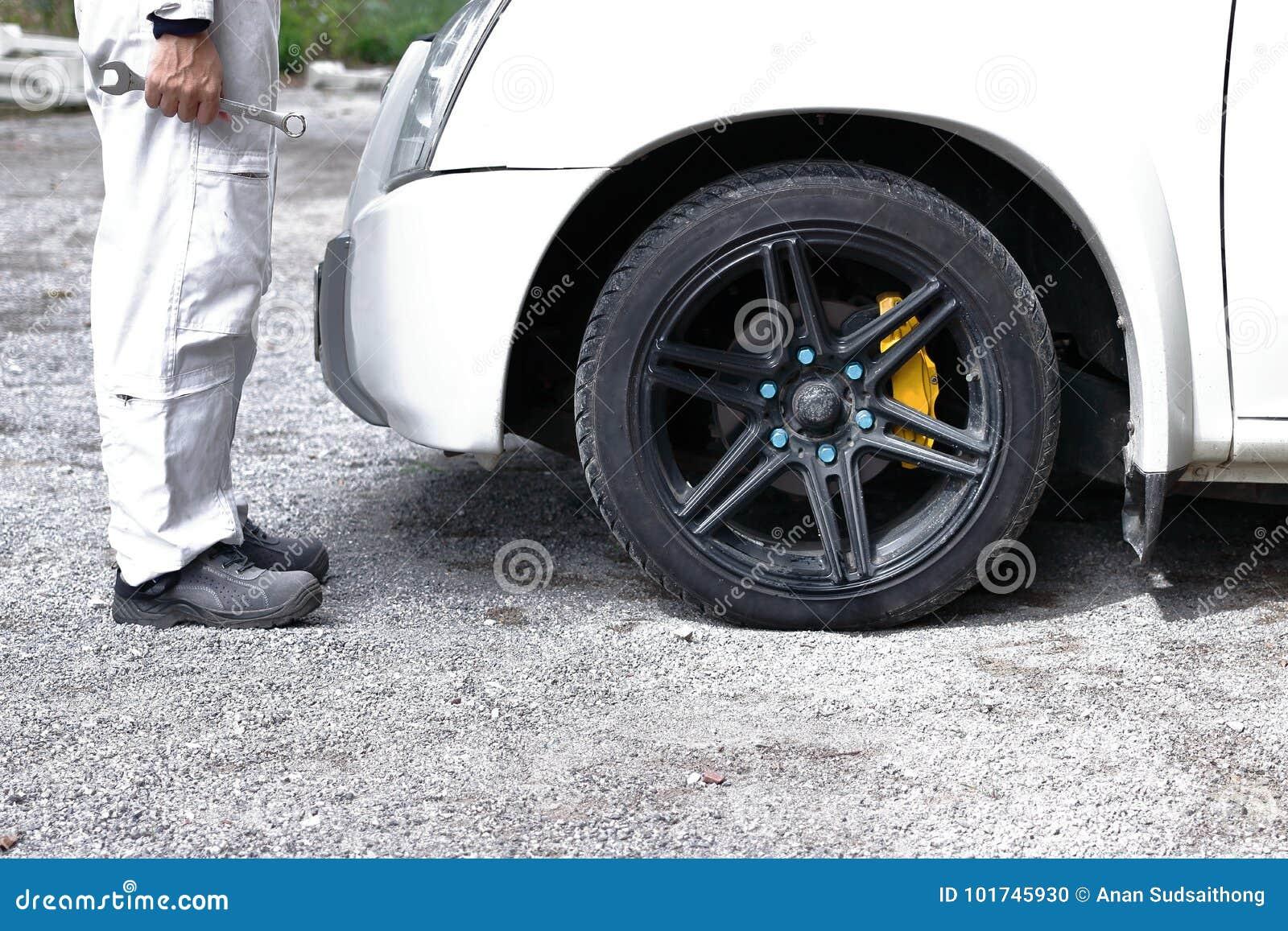 Vista laterale dell uomo automobilistico del meccanico in chiave della tenuta dell uniforme di bianco in sue mani pronte a ripara