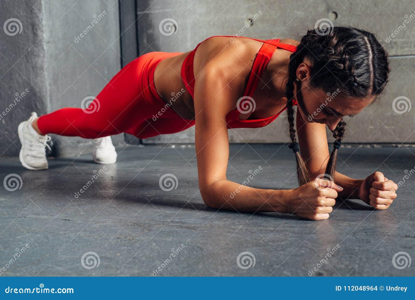 Vista laterale della donna di misura che fa esercizio del centro della plancia