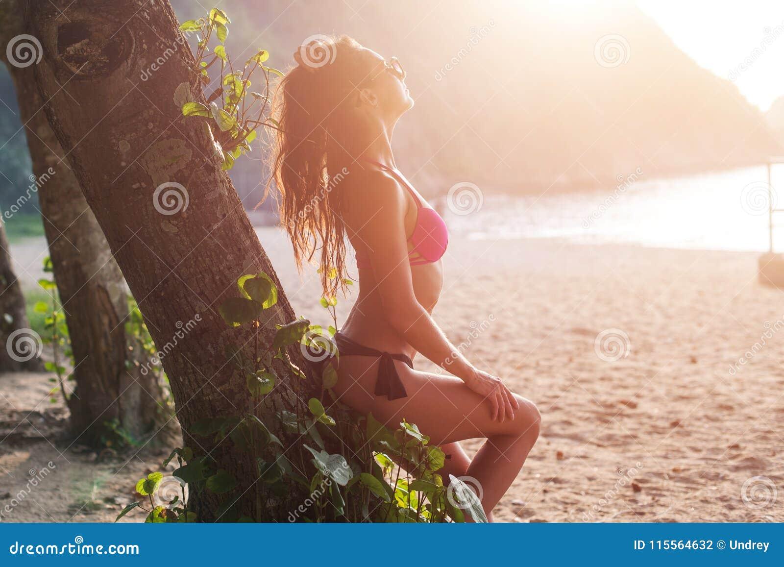 Vista laterale della giovane donna esile attraente in bikini che pende contro l albero che giudica i suoi capelli marroni posteri
