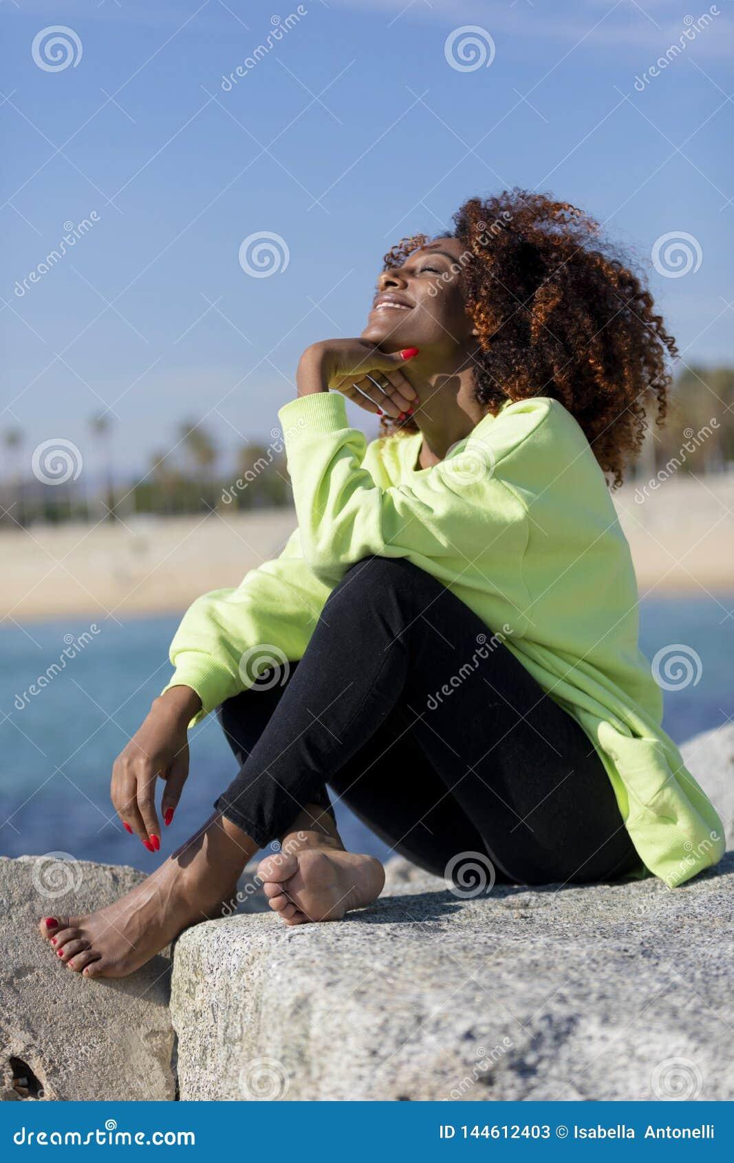 Vista laterale di bella donna riccia di afro che si siede sulle rocce del frangiflutti che ridono mentre riposando mano sotto gli
