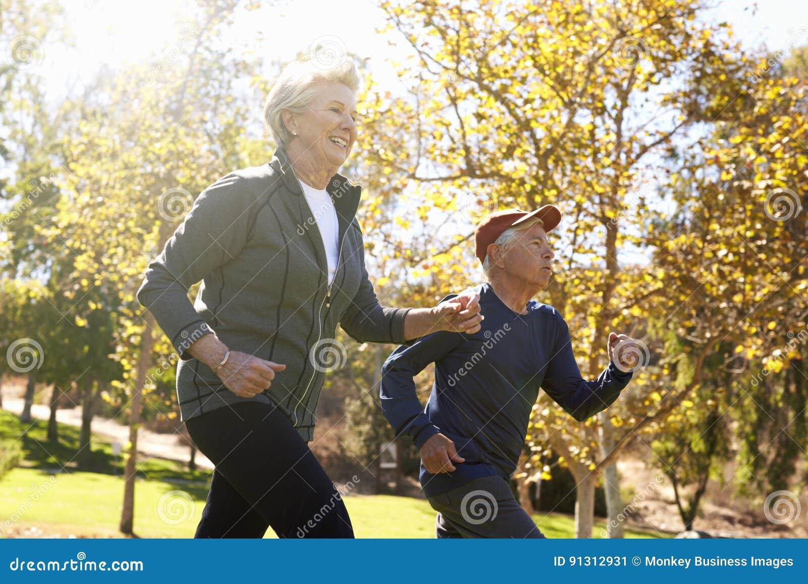 Vista laterale di potere senior delle coppie che cammina attraverso il parco