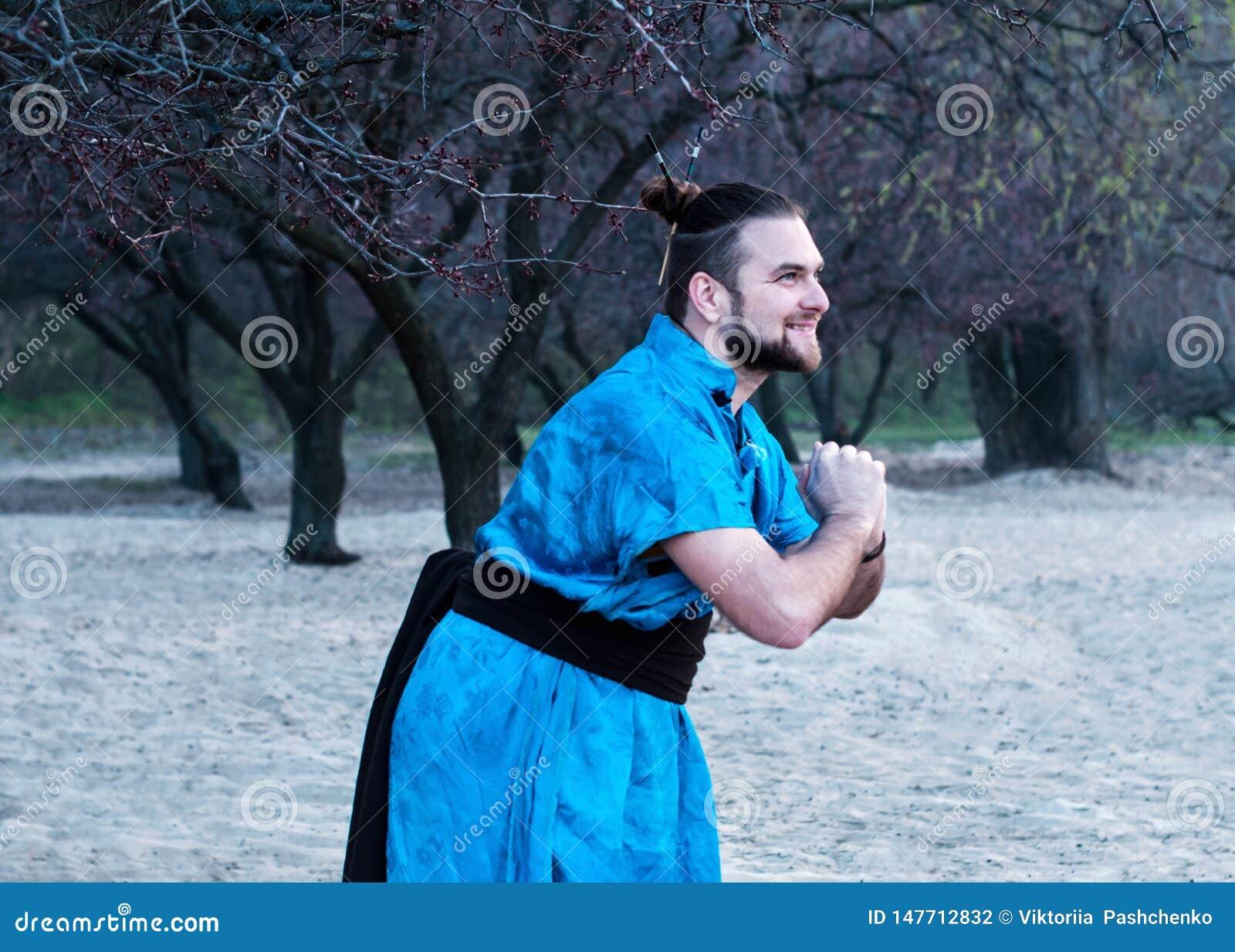 Vista laterale di risata dell uomo barbuto bello nella condizione blu del kimono con messo le mani