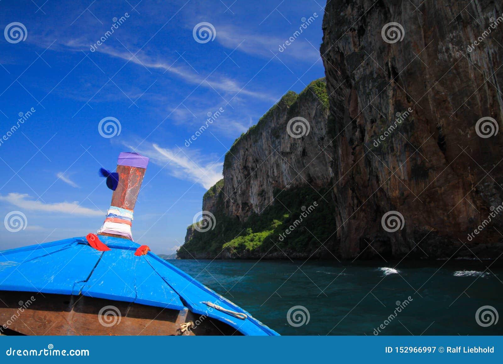 Vista na curva de madeira decorada azul do barco do longtail e da parede da rocha sob o céu azul com poucas nuvens de cirro