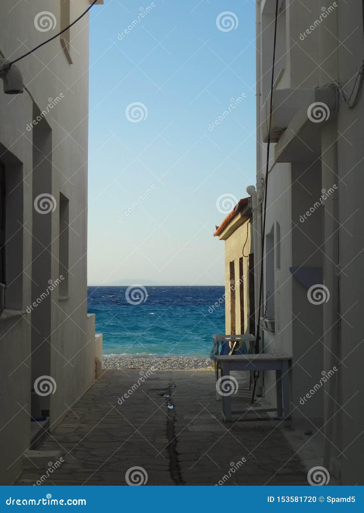 Vista no mar azul através de uma rua estreita