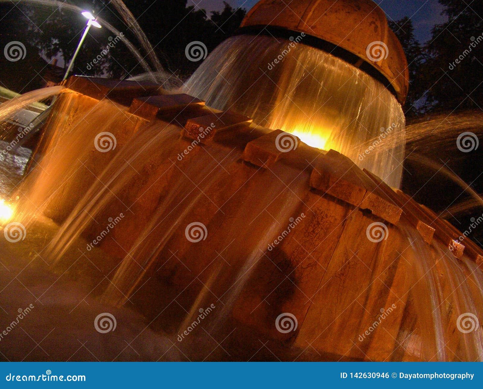 Vista nocturna de la agua corriente del parque de Herzel de la fuente local de la rana, iluminada por las luces ámbar calientes