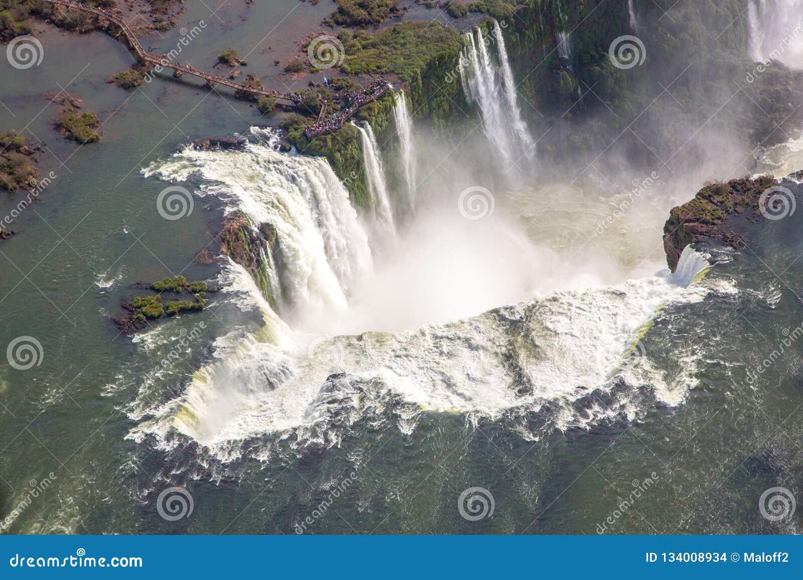 Vista panorámica aérea del arco iris hermoso sobre abismo de la garganta del diablo de las cataratas del Iguazú de un vuelo del h
