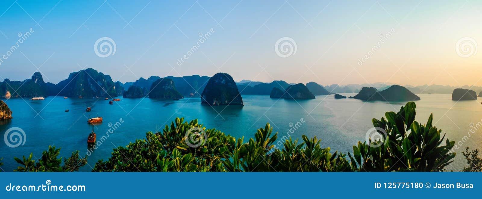 Vista panorámica de los barcos que flotan en las aguas tranquilas de la bahía Vietnam de Halong en la puesta del sol