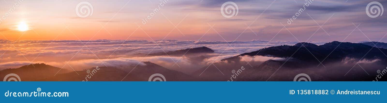 Vista panorámica de una puesta del sol sobre un mar de las nubes que cubren área de la Bahía de San Francisco del sur; cantos de
